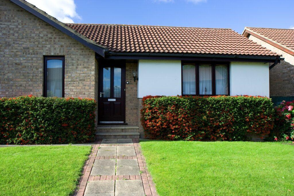 Dom rodzinny z zielonym trawnikiem i ścieżką.