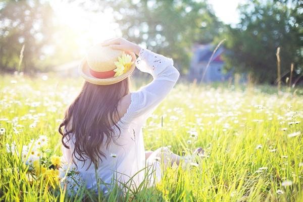 Kobieta z długimi, brązowymi włosami, w kapeluszu i białej koszuli siedzi tyłem na trawniku. Patrzy przed siebie na drzewa w oddali. Prawą ręką przytrzymuje kapelusz.